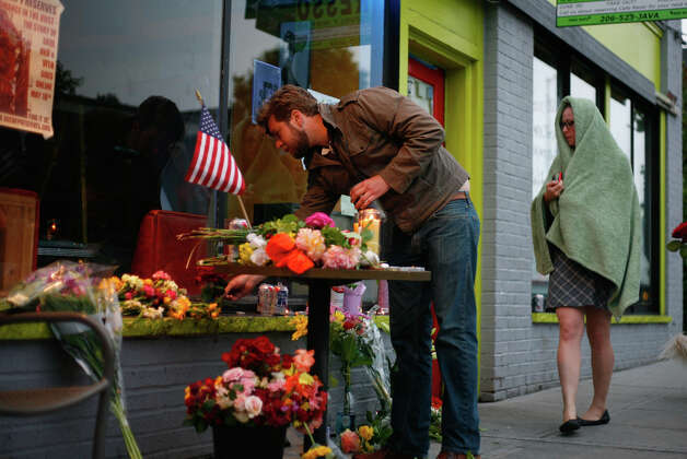 Flowers and candles are set in front of the Cafe Racer after five people were shot at the cafe. Four died there, a fifth in a separate shooting downtown and then the suspected shooter shot himself in West Seattle. He later died at Harborview. Photo: SOFIA JARAMILLO / SEATTLEPI.COM