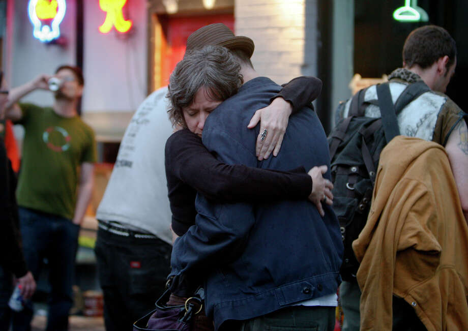 People embrace in front of Cafe Racer on Roosevelt Way NE in Seattle after a shooting there on May 30, 2012. Photo: SOFIA JARAMILLO / SEATTLEPI.COM