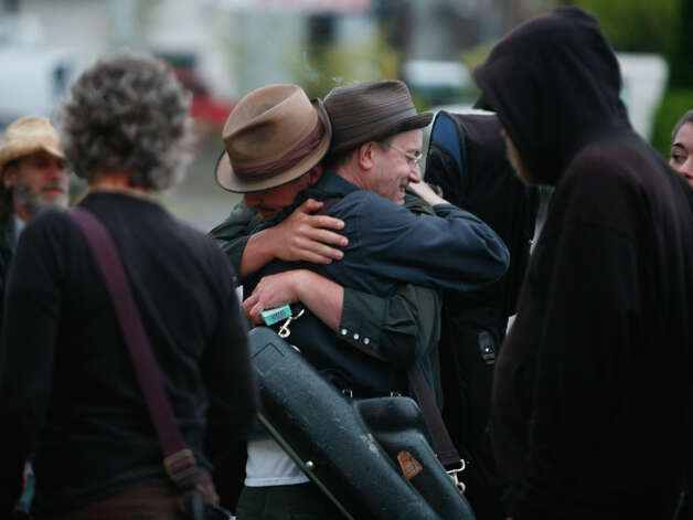 People embrace in front of Cafe Racer on Roosevelt Way NE in Seattle after a shooting there. Photo: SOFIA JARAMILLO / SEATTLEPI.COM