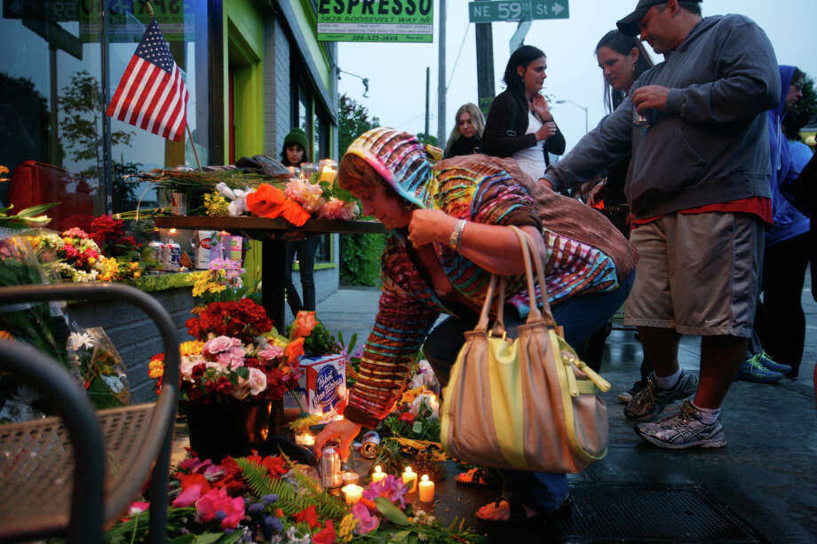 Flowers and candles are placed in front of the Cafe Racer on May 30, 2012, after five people were shot at Cafe Racer on Roosevelt Way Northeast in Seattle. Photo: SOFIA JARAMILLO / SEATTLEPI.COM