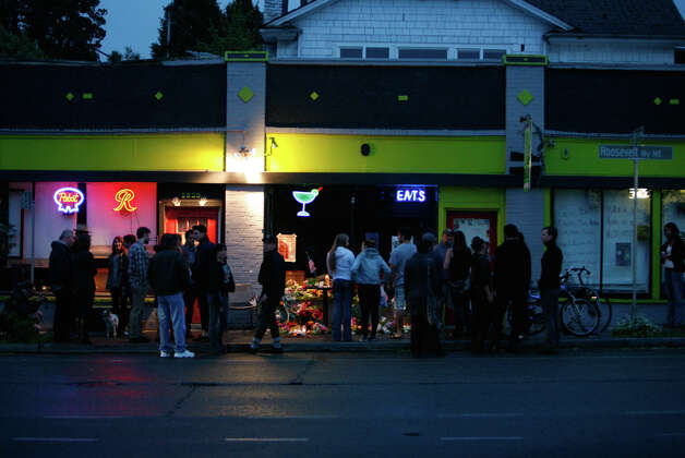 Mourners gather in front of the Cafe Racer after five people were shot at the cafe on Roosevelt Way NE in Seattle. Four of the victims died from the violence. A fifth person was shot and killed in downtown Seattle about 30 minutes later. Seattle Police said they believed it was by the same suspect. The suspect later shot himself in West Seattle. Photo: SOFIA JARAMILLO / SEATTLEPI.COM