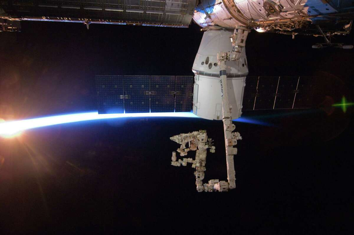 In this image provided by NASA with rays of sunshine and the thin blue atmosphere of Earth serving as a backdrop, the SpaceX Dragon commercial cargo craft is berthed to the Earth-facing side of the International Space Station's Harmony node Sunday May 27, 2012. Expedition 31 Flight Engineers Don Pettit and Andre Kuipers grappled Dragon at 9:56 a.m. (EDT) with the Canadarm2 robotic arm and used it to berth Dragon to the at 12:02 p.m. May 25, 2012. Dragon became the first commercially developed space vehicle to be launched to the station. Dragon is scheduled to spend about a week docked with the station before returning to Earth on May 31 for retrieval.