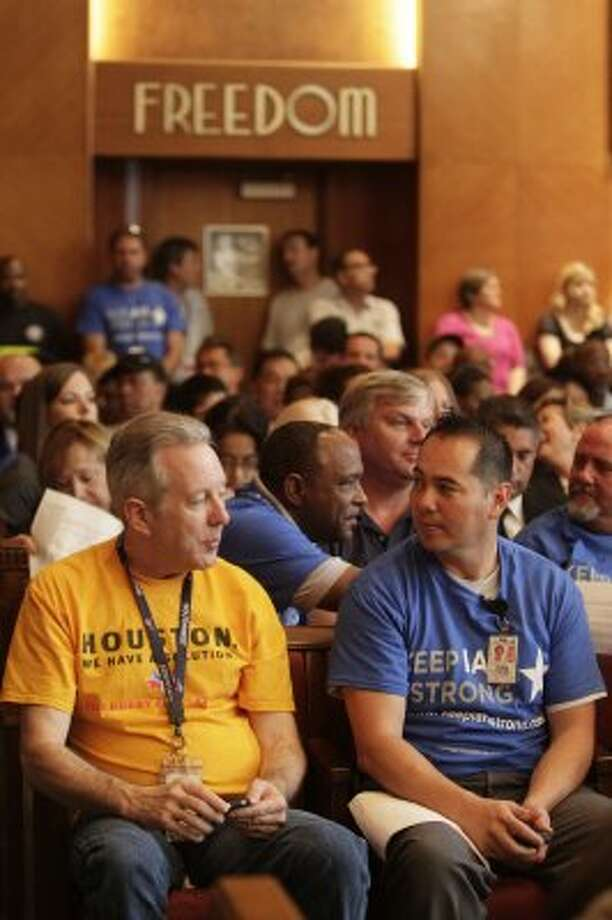 Southwest employee Scott Williams sits next to United employee Tuan Kincaid before the Houston City Council vote  on Wednesday, May 30, 2012, in Houston.  (Mayra Beltran / Associated Press)