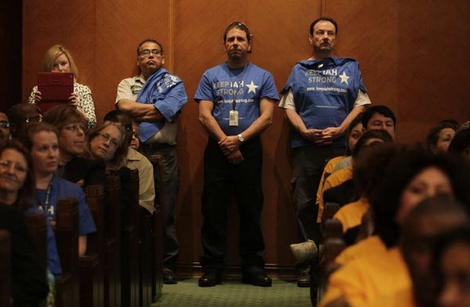 "United Airlines employees wearing ""Keep IAH (Bush Intercontinental Airport) Strong"" stand quietly while speakers address City Council before the vote Wednesday, May 30, 2012, in Houston.  (Mayra Beltran / Associated Press)"