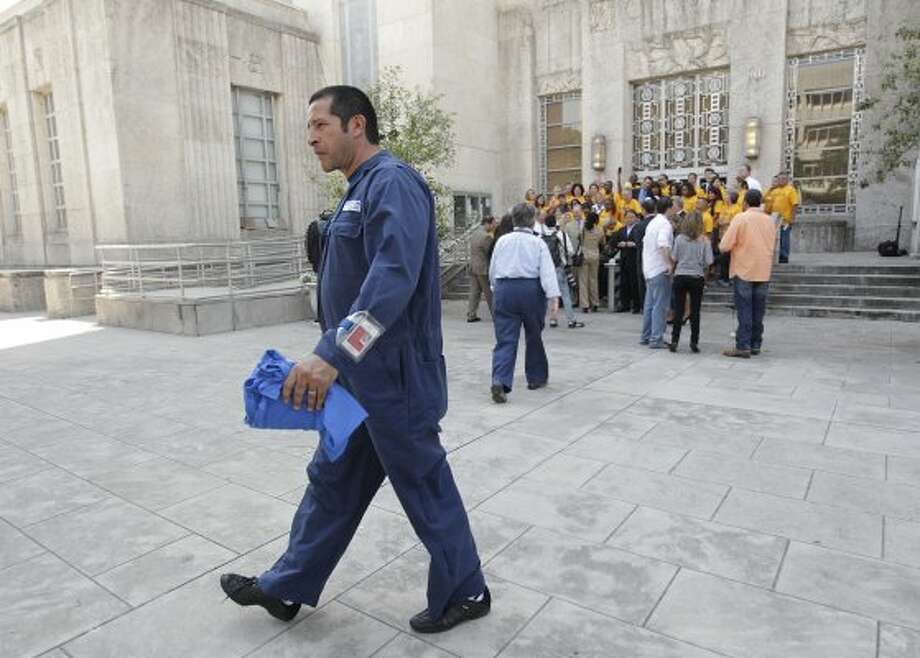Continental Airline employee walks past Southwest Airlines employees celebrating outside of City Houston after Council approved a $100 million expansion of Hobby Airport on Wednesday, May 30, 2012, in Houston.  (Mayra Beltran / Associated Press)