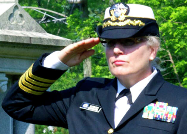 Kathleen Lindenmayer, a U.S. Navy captain, offers a salute Monday during a Memorial Day ceremony in the St. Andrew's Church cemetery in Kent. May 28, 2012 Photo: Trish Haldin