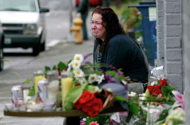 Stacy Davis cries as she sits near a growing memorial at the scene of where a gunman killed four people and severely wounded another in a cafe a day earlier, Thursday, May 31, 2012, in Seattle. Police say he later killed a woman during a carjacking before shooting himself. As officers closed in during a widespread manhunt on Wednesday, the suspect put a gun to his head and pulled the trigger and later died at a hospital. (AP Photo/Elaine Thompson) Photo: Elaine Thompson, Associated Press / AP