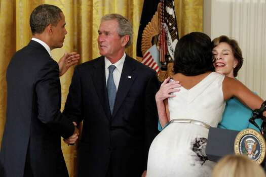 President Barack Obama and first lady Michelle Obama embrace former President George W. Bush and former first lady Laura Bush during the unveiling of their official portraits in the East Room at the White House in Washington, Thursday, May 31, 2012. Photo: Charles Dharapak, Associated Press / AP