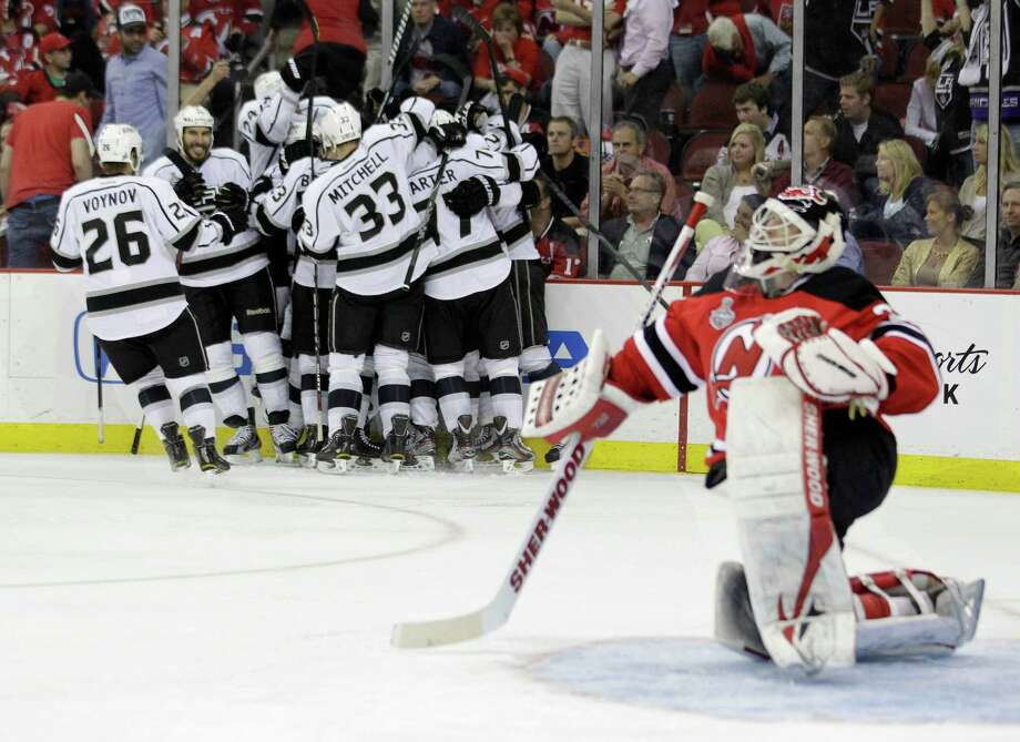 New Jersey Devils' goalie Martin Brodeur gets up from the ice after as the Los Angeles Kings celebrate their winning goal during the overtime period of Game 1 of the NHL hockey Stanley Cup finals Wednesday, May 30, 2012  in Newark, N.J.  The Kings won the game 2-1. (AP Photo/Julio Cortez) Photo: Julio Cortez, Associated Press / AP
