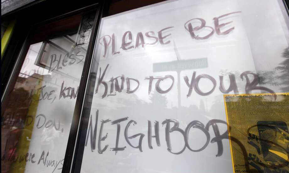 A message is written Thursday on paper  covering the window at the front of Cafe Racer where a gunman killed four  people and severely wounded another a day earlier. (AP Photo/Elaine  Thompson)