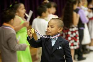 Ronaldo Torres holds up his award for perfect attendance during a kindergarten promotion ceremony at Lyons Elementary School Thursday, May 31, 2012, in Houston. The students will start first grade next year.