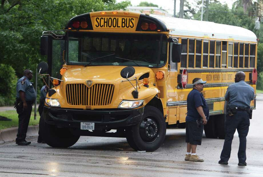 HISD officials look over a school bus which was involved in a two vehicle accident at the intersection of Montrose Boulevard and Sul Ross Street Thursday, May 31, 2012, in Houston. There were no reported injuries to the students or drivers of both vehicles. Photo: James Nielsen, Chronicle / © Houston Chronicle 2012