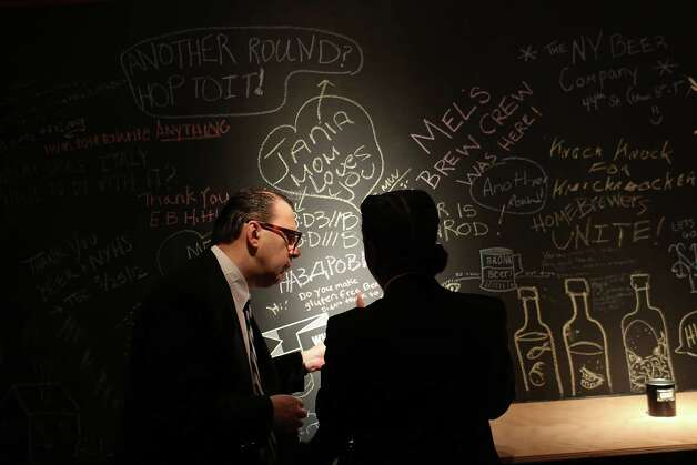 NEW YORK, NY - MAY 30: Two museum employees speak in front of a chalk board where museum visitors can write their thoughts concerning beer at the new exhibition at the New York Historical Society called Beer Here: Brewing New York's History on May 30, 2012 in New York City. The exhibition looks to celebrate New York's largely neglected history as an important participant in the production and consumption of beer, ale, and porter from the seventeenth century to the present. The exhibition, which goes on until September 2, includes numerous displays on early brewing in New York including an actual beer hall featuring  a selection of favorite New York City and State artisanal beers. Photo: Spencer Platt, Getty Images / 2012 Getty Images