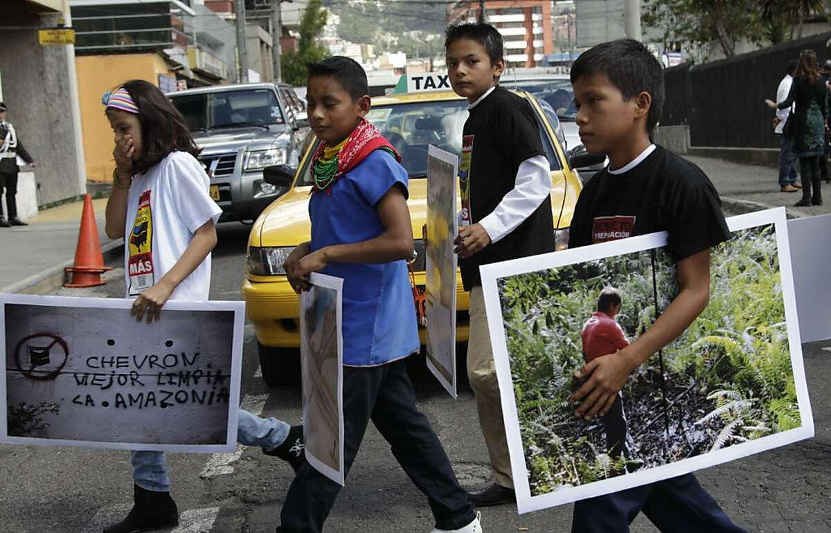Children from the Amazonian region make their way into the National Court during a protest against Chevron, in Quito, Ecuador, Thursday, May 31, 2012. Plaintiffs who won an $18 billion pollution judgment against Chevron Corp. in Ecuador say they've begun their campaign to collect the money, filing suit against the company in Canada. (AP Photo/Dolores Ochoa)