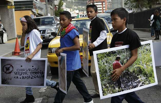 Children from the Amazonian region make their way into the National Court during a protest against Chevron, in Quito, Ecuador, Thursday, May 31, 2012. Plaintiffs who won an $18 billion pollution judgment against Chevron Corp. in Ecuador say they've begun their campaign to collect the money, filing suit against the company in Canada. (AP Photo/Dolores Ochoa) Photo: Dolores Ochoa, Associated Press