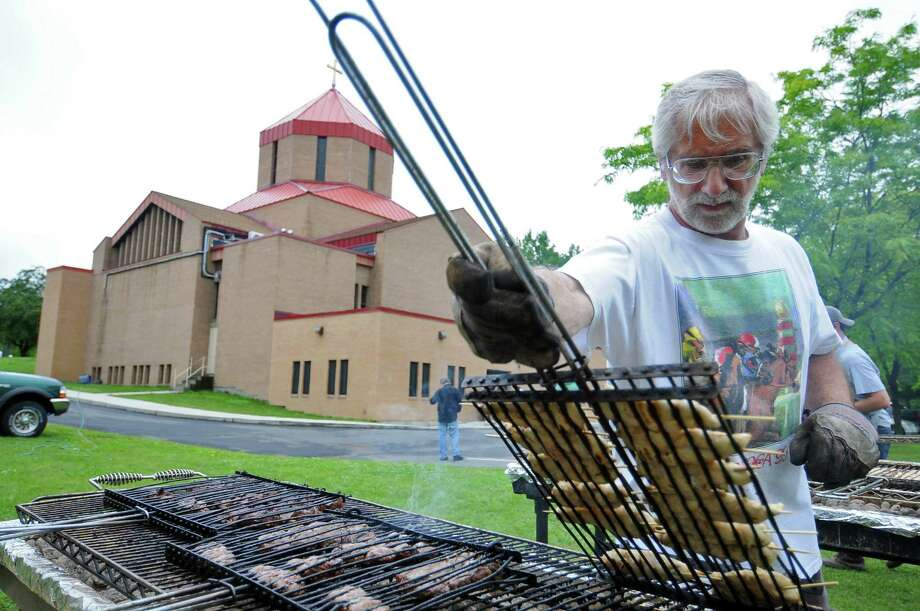"Ron Kaiser checks on chicken kebabs cooking on a grill during the Armenian Festival 2010 at St. Peter Armenian Church in Watervliet, NY on Sunday June 13, 2010.  John ""Frenchie"" Ekmalian, festival chairman, Chuck Tutunjian and Eddie Belemegjian, members of the church, had started preparing shish kebab (lamb) and losh kebab (ground beef and spices) a week ago, marinating them for 24 hours before freezing them. The chicken was also marinated for 24 hours, nearer to the weekend. 854 chicken kebabs were prepared, along with 1082 shish kebabs and 1255 losh kebabs, according to  Ekmalian.( Philip Kamrass / Times Union) Photo: PHILIP KAMRASS / 00009111A"