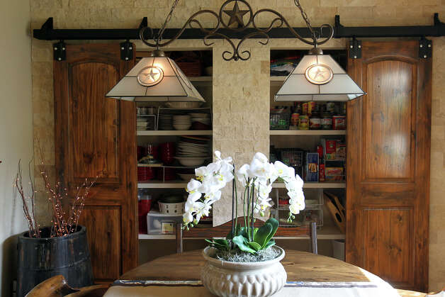 Hidden pantry in the dining room with doors hung on a steel barn wood sliding door track and hand distressed by their interior designer daughter, Jenney Munguia, in the Kuhn home in Boerne, Saturday, May 26, 2012. (JENNIFER WHITNEY) Photo: JENNIFER WHITNEY, Jennifer Whitney/ Special To The Express-News / special to the Express-News