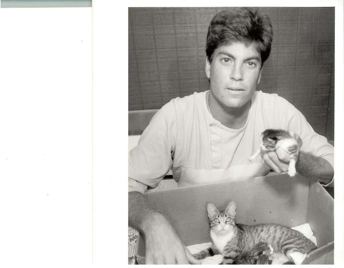 Golden Gators pitcher Steve Schefsky holds one of Dugout the cat's kittens in his hand while Dugout and three other kittens sit in a box. Dugout was the Golden Gators' adopted mascot.