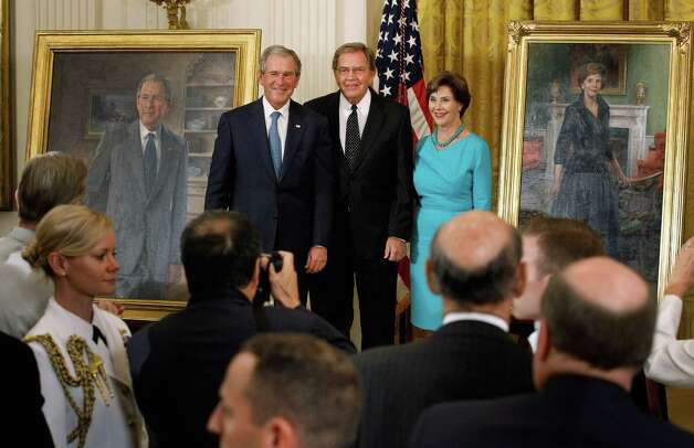Former President George W. Bush (L) and former first lady Laura Bush (R) pose with artist John Howard Sanden during the unveiling ceremony of the Bushs' offical portraits in the East Room of the White House May 31, 2012 in Washington, DC. Commissioned by the White House Historical Association, the portraits will hang in the White House next to portraits of the other past presidents. Photo: Chip Somodevilla, Getty Images / 2012 Getty Images
