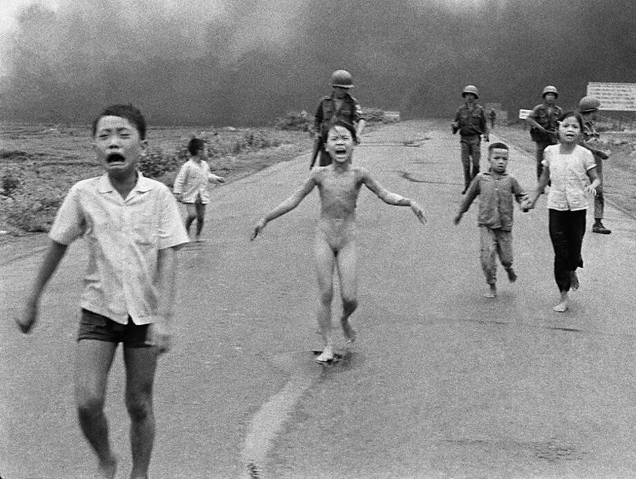 FILE - In this June 8, 1972 file photo, crying children, including 9-year-old Kim Phuc, center, run down Route 1 near Trang Bang, Vietnam after an aerial napalm attack on suspected Viet Cong hiding places as South Vietnamese forces from the 25th Division walk behind them. A South Vietnamese plane accidentally dropped its flaming napalm on South Vietnamese troops and civilians. From left, the children are Phan Thanh Tam, younger brother of Kim Phuc, who lost an eye, Phan Thanh Phouc, youngest brother of Kim Phuc, Kim Phuc, and Kim's cousins Ho Van Bon, and Ho Thi Ting. (AP Photo/Nick Ut) Photo: Nick Ut, Associated Press
