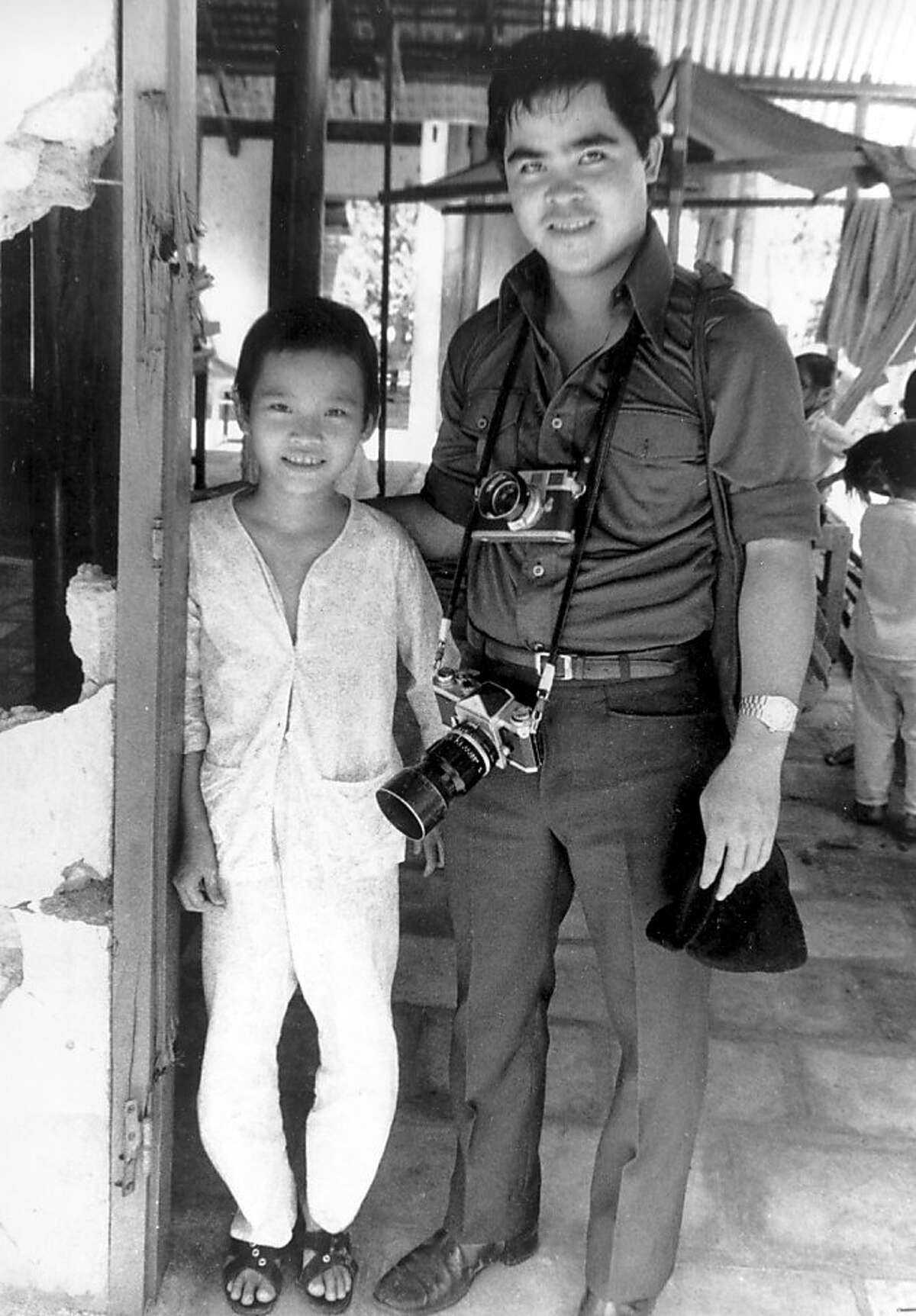 FILE - In this 1973 file photo, Phan Thi Kim Phuc, left, is visited by Associated Press photographer Nick Ut at her home in Trang Bang, Vietnam. As a nine-year-old, Kim Phuc was the subject of a Pulitzer Prize-winning photo by Ut as she fled in pain from a misdirected napalm attack against her village by South Vietnamese planes in 1972. After taking the photograph, Ut came to the girl's aid and transported her to a hospital. (AP Photo)