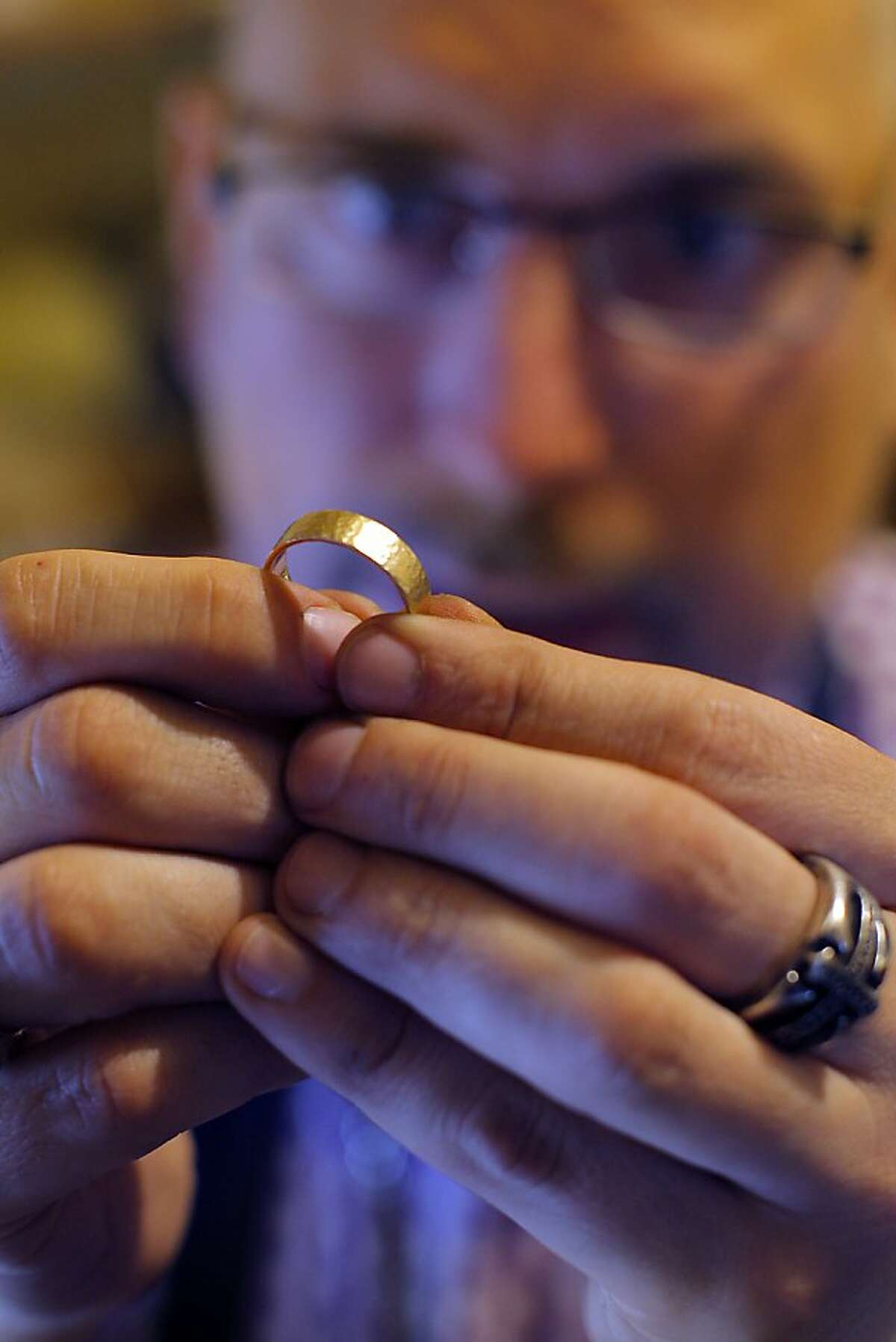 Shawn Higgins inspects a gold wedding bend he just finished working on in the back of his eco jewels store in the Castro, San Francisco, Calif. on May 14, 2012.