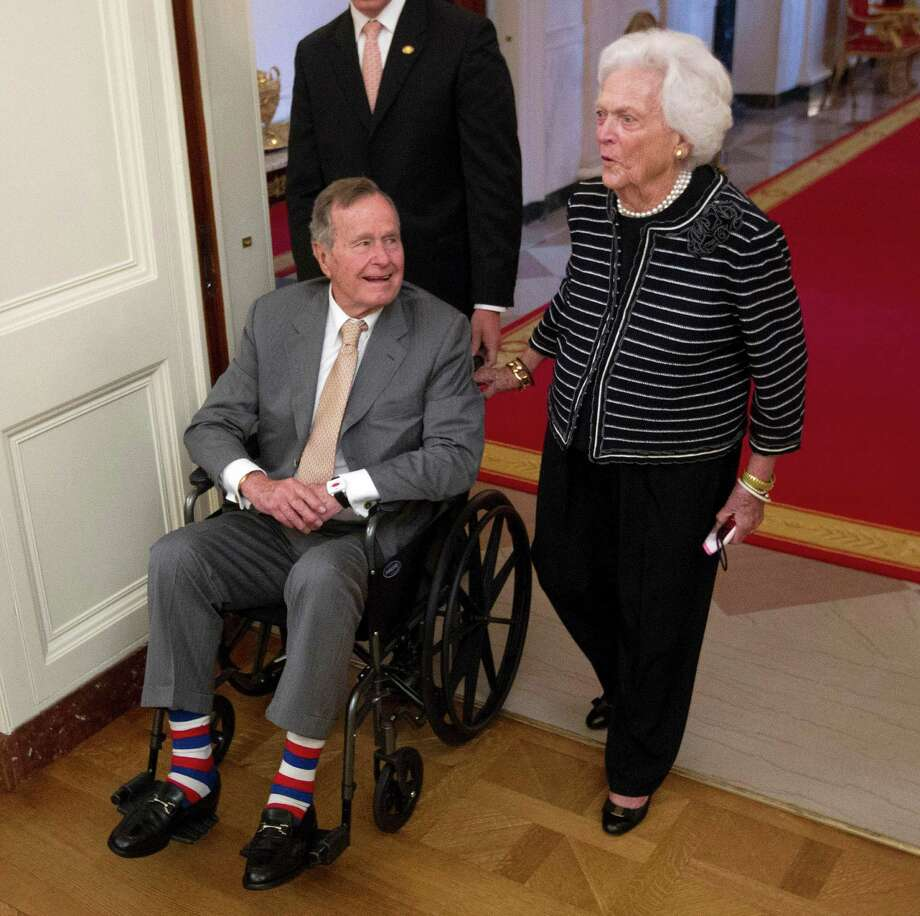 Former President George H.W. Bush, left, and his wife, former first lady Barbara Bush, arrive in the East Room of the White House on Thursday for the unveiling ceremony. Photo: Pablo Martinez Monsivais / AP
