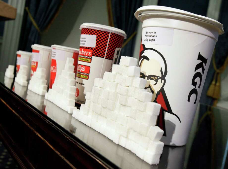 Various size cups and sugar cubes are displayed at a news conference at New York's City Hall, Thursday. New York Mayor Michael Bloomberg is proposing a ban on the sale of large sodas and other sugary drinks in the hopes of combating obesity. Photo: Richard Drew / AP