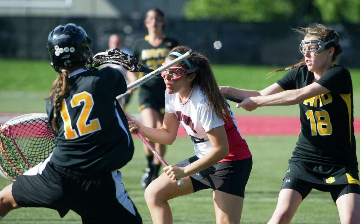 New Canaan's Kristin Ryan looks to shoot as Hand's Hannah Johnson, left, and goalie Christy Forrest defend as New Canaan High School hosts Daniel Hand in a Class M girls lacrosse game in New Canaan, Conn., May 31, 2012.