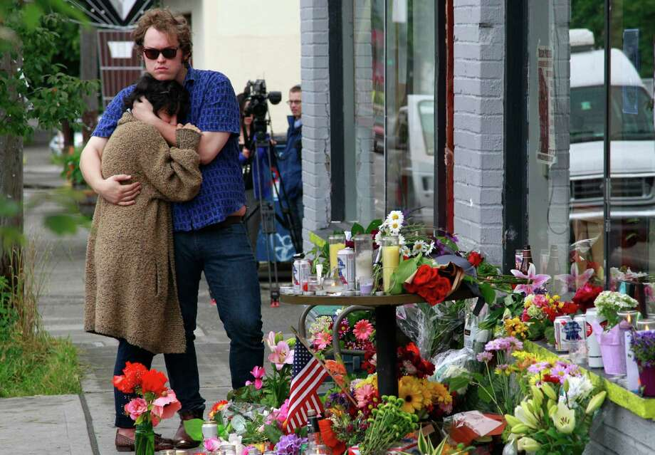 Jonny and Ali, who both declined to give their last names, react Thursday to the makeshift memorial at a Seattle cafe where a gunman killed four people and wounded another a day earlier. The pair were friends of two of the victims. Photo: Elaine Thompson / AP