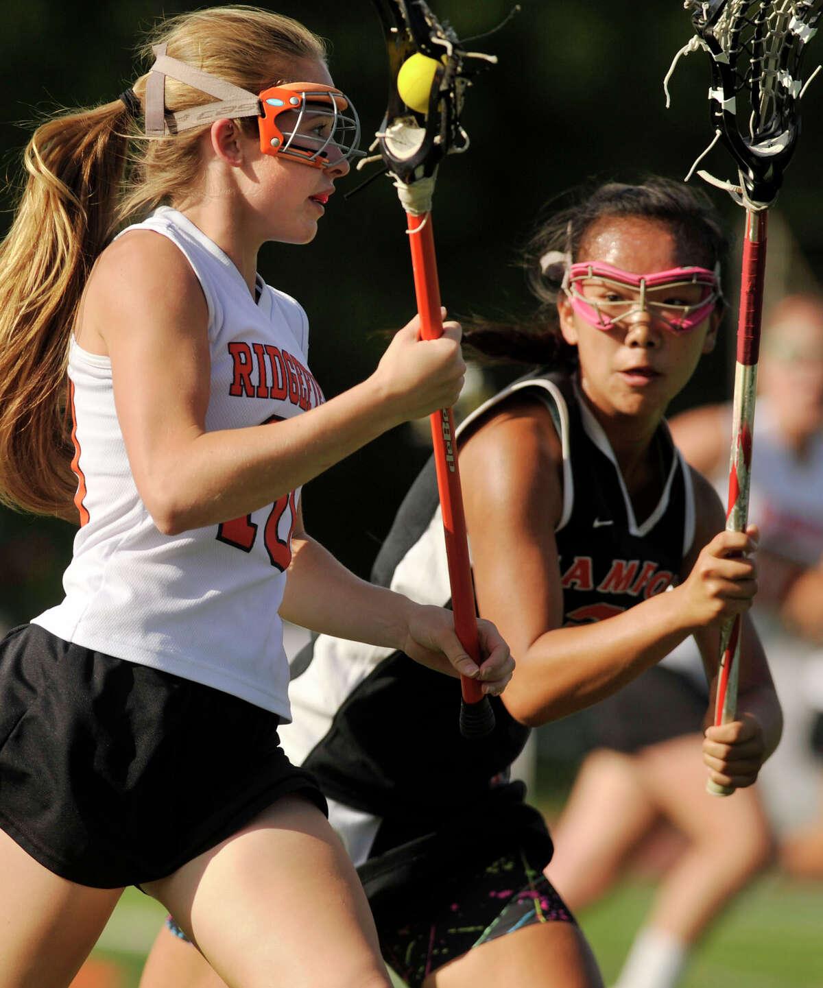 Ridgefield's Megan Kirchoff runs into resistance from Stamford's Jasmine Li during their Class L state tournament game at Ridgefield on Thursday, May 31, 2012. Ridgefield won 16-9.