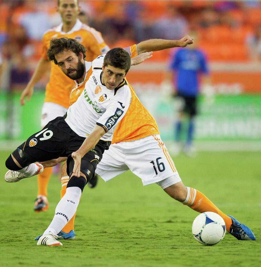 Houston Dynamo midfielder Adam Moffat (16) tangles with Valencia midfielder Pablo Hernandez (19) during first half of the BBVA Compass Dynamo Charities Cup friendly soccer match on Thursday, May 31, 2012, at BBVA Compass Stadium in Houston. Photo: Smiley N. Pool, Houston Chronicle / © 2012  Houston Chronicle