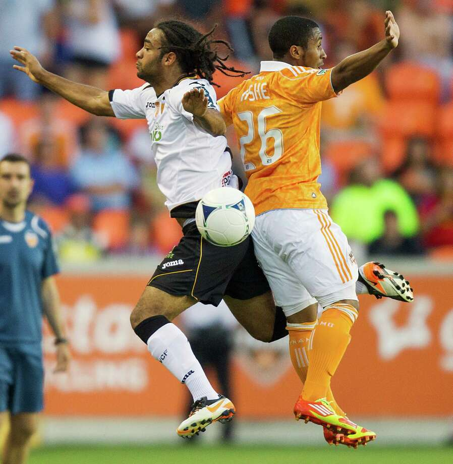Dynamo midfielder Corey Ashe (26) fights for a ball against Valencia midfielder Joel Johnson (17). Photo: Smiley N. Pool, Houston Chronicle / © 2012  Houston Chronicle