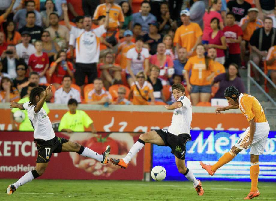 Dynamo forward Galen Carr (3) splits the defense of Valencia midfielder Joel Johnson (17) and defender Angel Dealbert (15) for a goal. Photo: Smiley N. Pool, Houston Chronicle / © 2012  Houston Chronicle