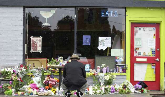 A man squats in front of makeshift memorial outside Cafe Racer May 31, 2012 in Seattle, Washington. Before killing Leonidas, the gunman, reportedly identified as Ian Lee Stawickiallegedly, 40, shot and killed four at cafe in another part town. He then killed himself as police approached. Photo: Stephen Brashear, Getty Images / 2012 Getty Images