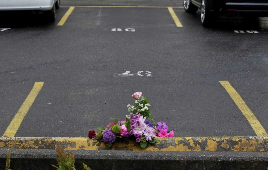 Flowers lie in the parking lot where Gloria Koch Leonidas was killed May 31, 2012 in Seattle, Washin
