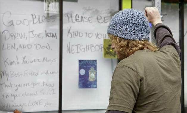 Reilly Donovan leans on a signpost in front of a note written on the windows of Cafe Racer May 31, 2012 in Seattle, Washington. Photo: Stephen Brashear, Getty Images / 2012 Getty Images