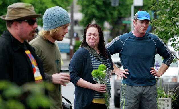 Friends and neighbors stand at the scene of where a gunman killed four people and severely wounded another in a cafe a day earlier, Thursday, May 31, 2012, in Seattle. Photo: Elaine Thompson, Associated Press / AP