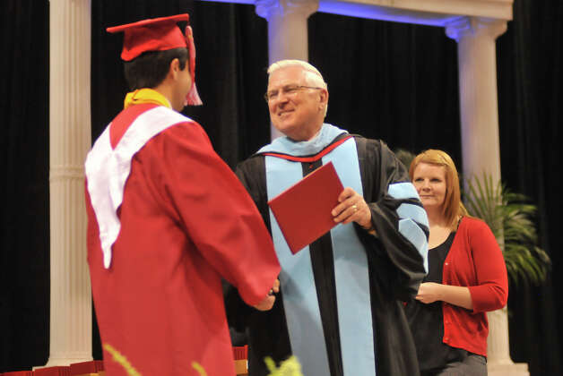 Superintendent John Folks hands out diploma's during one of his last high school graduations  Thursday evening in the Alamodome for Taft High School and Communications Arts High School. Photo: For The Express-News, Robin Jerstad