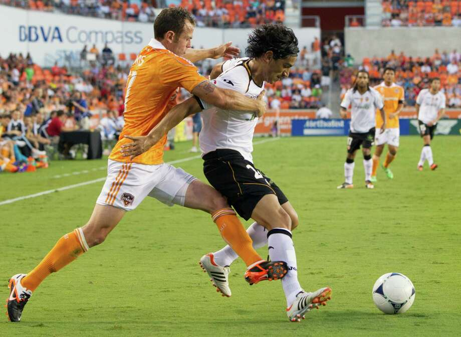 Houston Dynamo midfielder Brad Davis (11) tussles with Valencia midfielder Tino Costa (24) during first half of the BBVA Compass Dynamo Charities Cup friendly soccer match on Thursday, May 31, 2012, at BBVA Compass Stadium in Houston. Photo: Smiley N. Pool, Houston Chronicle / © 2012  Houston Chronicle