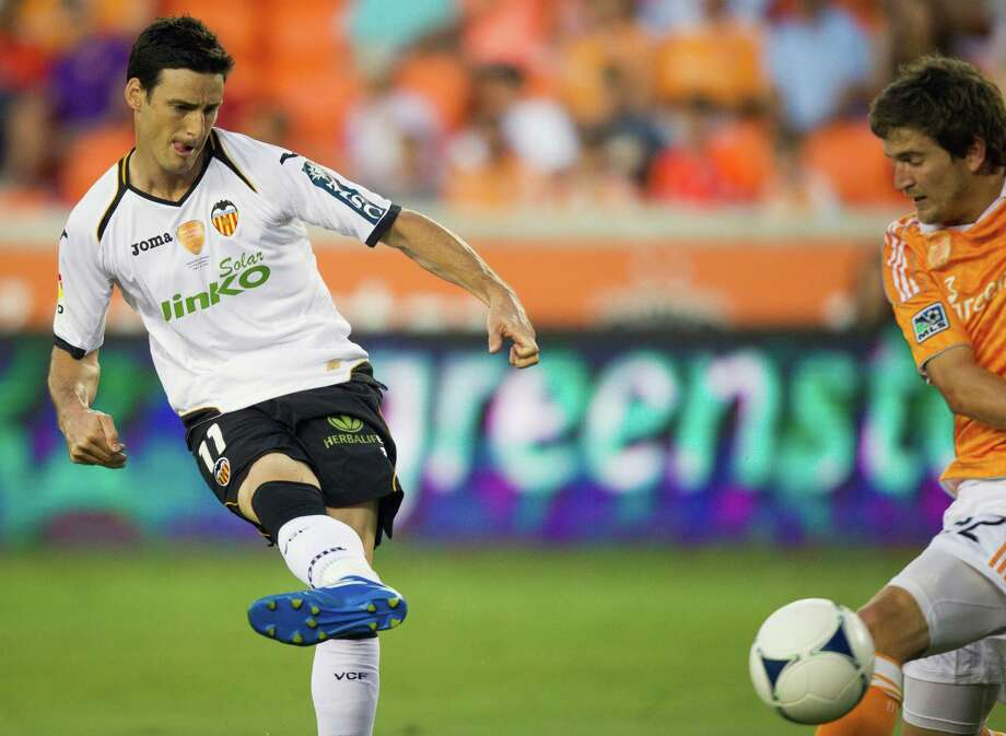 Valencia forward Aritz Aduriz (11) slips the ball past Houston Dynamo defender Bobby Boswell for a goal during first half of the BBVA Compass Dynamo Charities Cup friendly soccer match on Thursday, May 31, 2012, at BBVA Compass Stadium in Houston. Photo: Smiley N. Pool, Houston Chronicle / © 2012  Houston Chronicle