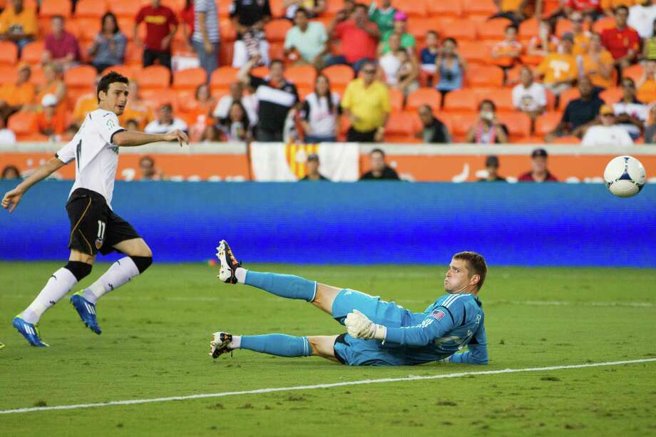 Valencia forward Aritz Aduriz slips the ball past Houston Dynamo goalkeeper Tyler Deric for a goal during first half of the BBVA Compass Dynamo Charities Cup friendly soccer match on Thursday, May 31, 2012, at BBVA Compass Stadium in Houston. Photo: Smiley N. Pool, Houston Chronicle / © 2012  Houston Chronicle
