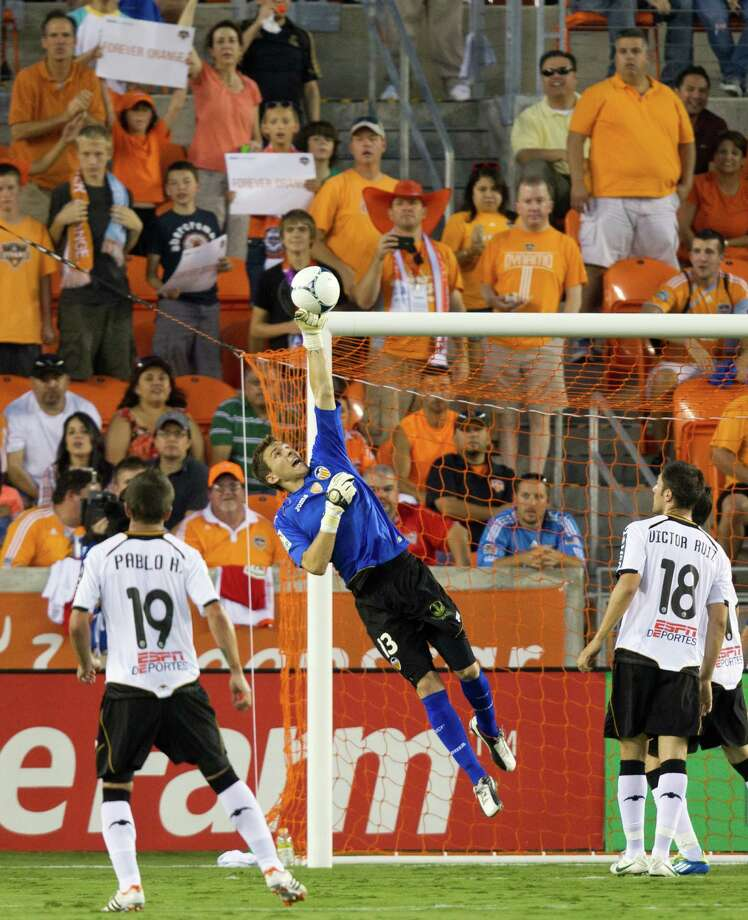 Valencia goalkeeper Vicente Guaita (13) punches a Houston Dynamo shot away from the net during first half of the BBVA Compass Dynamo Charities Cup friendly soccer match on Thursday, May 31, 2012, at BBVA Compass Stadium in Houston. Photo: Smiley N. Pool, Houston Chronicle / © 2012  Houston Chronicle