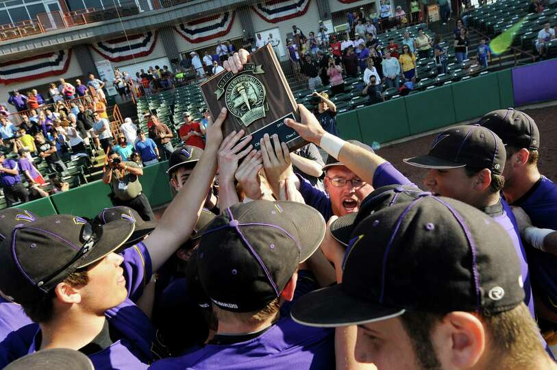 Voorheesville coach Kyle Turski, center, holds up the winner's plaque for his team to touch when the