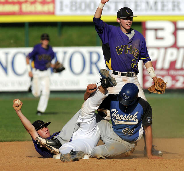 Voorheesville's short stop Mike Young (34), left, holds up the ball after tagging out Hoosick Falls'