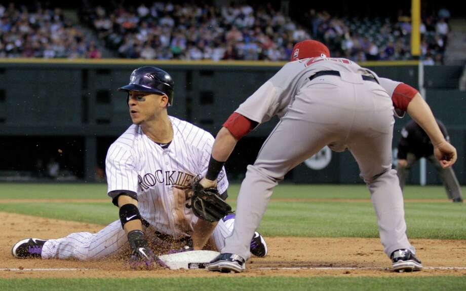 Colorado Rockies Carlos Gonzalez, left, steals third base against Houston Astros third baseman Chris Johnson in the fourth inning of a baseball game on Thursday, May 31, 2012, in Denver. (AP Photo/Joe Mahoney) Photo: Joe Mahoney, Associated Press / FR170458 AP