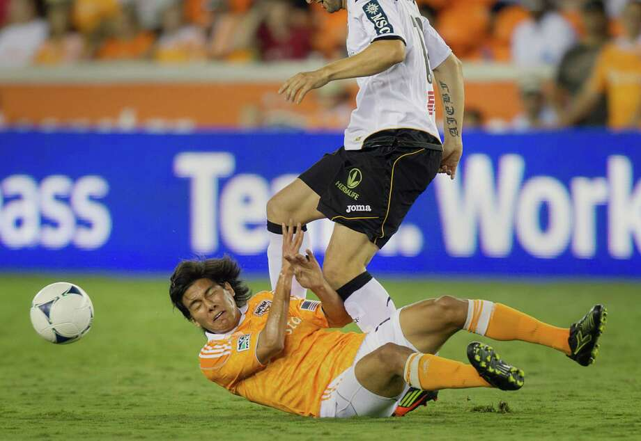 Houston Dynamo midfielder Josuej Soto (18) hits the turf as he loses a challenge to Valencia defender Antonio Barragan (12) during second half of the BBVA Compass Dynamo Charities Cup friendly soccer match on Thursday, May 31, 2012, at BBVA Compass Stadium in Houston. Valencia won the game 2-1. Photo: Smiley N. Pool / © 2012  Houston Chronicle