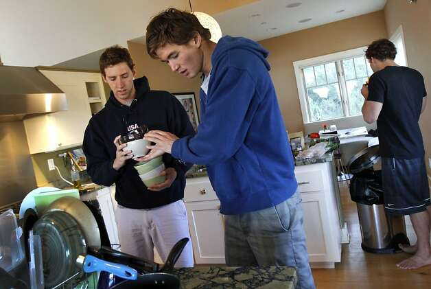 Swimmers Nathan Adrian, 23, center, and Will Copeland, 26, left, clean up the kitchen of their shared house in Berkeley, Calif. Monday, May 28, 2012.  The two live with fellow swimmers Sean Mahoney, 23, and Graeme Moore, 23, and have all been training for the Olympics together at the University of California. Photo: Sarah Rice, Special To The Chronicle