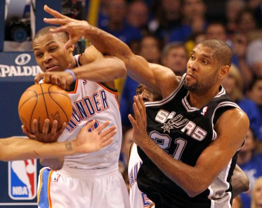 Oklahoma City Thunder's Russell Westbrook (0) passes under pressure from San Antonio Spurs' Tim Duncan (21) during the second half of game three of the NBA Western Conference Finals in Oklahoma City, Okla. on Thursday, May 31, 2012. (Kin Man Hui / Kin Man Hui / San Antonio Express-News)