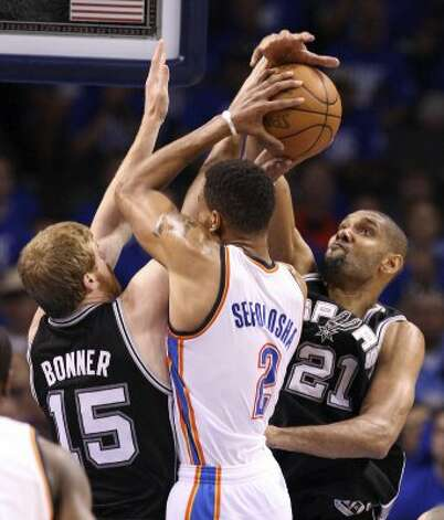 Oklahoma City Thunder's Thabo Sefolosha (2) is pressured at the rim by San Antonio Spurs' Matt Bonner (15) and San Antonio Spurs' Tim Duncan (21) during the second half of game three of the NBA Western Conference Finals in Oklahoma City, Okla. on Thursday, May 31, 2012. (Edward A. Ornelas / Edward A. Ornelas / San Antonio Express-News)